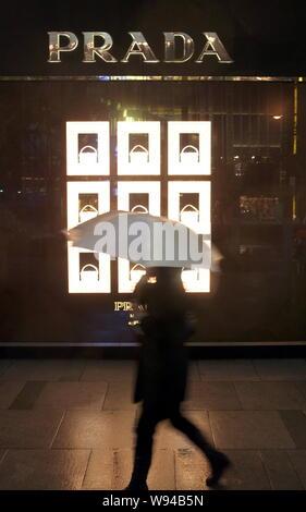 --FILE--A pedestrian walks past a Prada store in Shanghai, China, 13 December 2010.   Prada, Italys luxury goods powerhouse, said global sales were so - Stock Photo