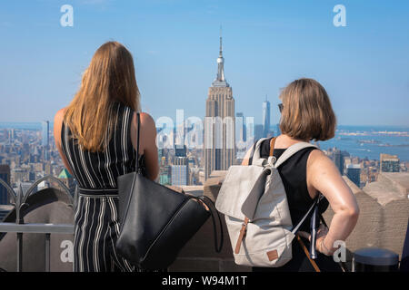 Women tourism, rear view of two female tourists looking over Midtown Manhattan from the Rockefeller Center Observation Deck, New York City, USA - Stock Photo