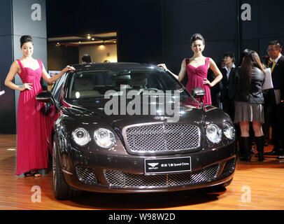 --FILE--Models pose next to a Bentley Continental Flying Spur during the 8th China (Guangzhou) International Automobile Exhibition, known as Auto Guan - Stock Photo