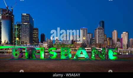 From  the illuminated 'Brisbane' artwork at Southbank Parklands, Brisbane, Australia, the lights of the city are switching on as night falls. - Stock Photo