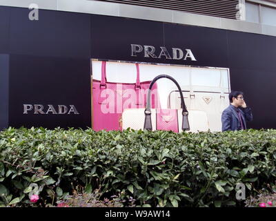 --File-- A Chinese man stands outside a Prada store in Shanghai, China, December 14, 2009.   Top global luxury brands like Burberry and Coach are pour - Stock Photo