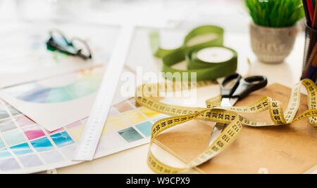 Closeup Of Fashion Designer Workplace With Measuring Tape And Color Samples - Stock Photo