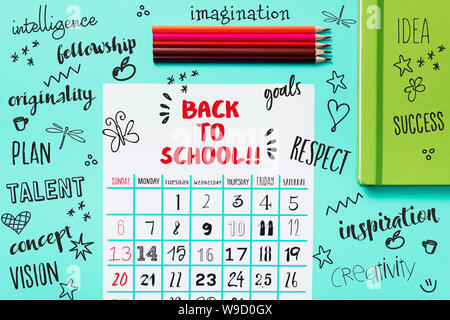 high angle view of a calendar with the text back to school on a blue table, next to some pencil crayons of different colors and a green notepad, and s - Stock Photo
