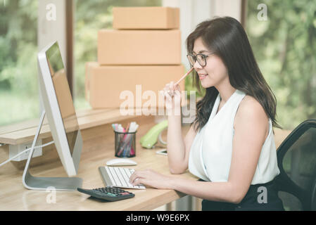 Young entrepreneur working on the smart computer at home office. - Stock Photo