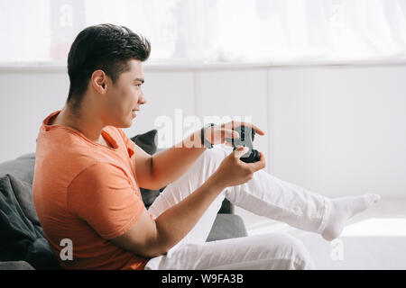 KYIV, UKRAINE - JUNE 12, 2019: Young asian man playing video game with joystick while sitting on couch at home. - Stock Photo
