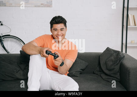 KYIV, UKRAINE - JUNE 12, 2019: Excited asian man playing video game while sitting on couch at home. - Stock Photo