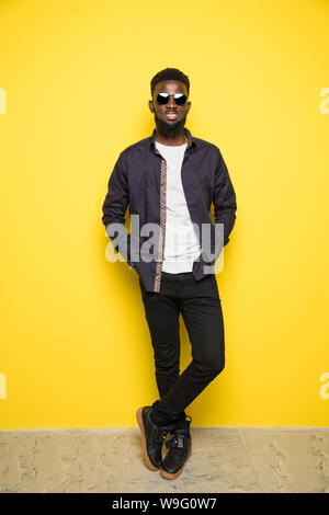 Young african man in sunglasses on yellow background - Stock Photo