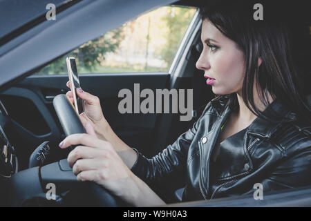 Profile view of young attractive woman looking at her smartphone while driving a car on a warm day. Female driver in leather jacket checking cellphone - Stock Photo
