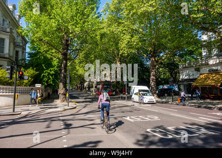 Traffic on tree lined Holland Park Avenue, Royal Borough of Kensington and Chelsea, London, UK - Holland Park Avenue London - Stock Photo