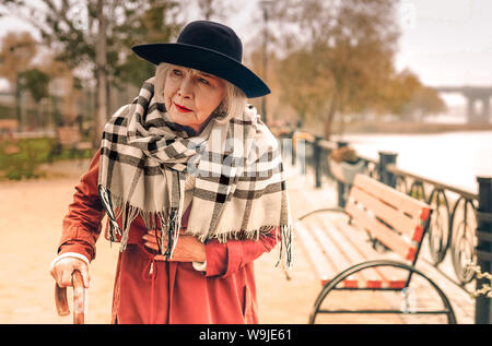 Senior stylish lady taking a walk in park suddenly experiencing chest pain - Stock Photo