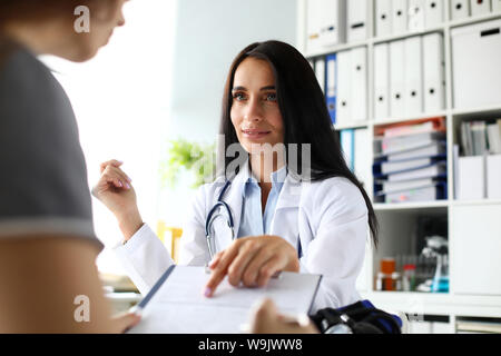 Beautiful caucasian female GP pointing finger in application form - Stock Photo