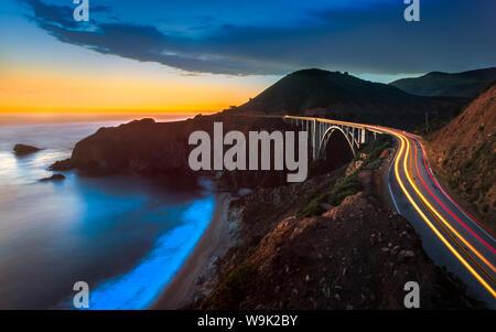 Sunset over Bixby Creek Bridge and car trail lights, Big Sur, California, United States of America, North America - Stock Photo