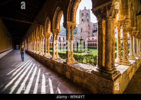 Tourist at Duomo di Monreale (Monreale Cathedral) in the courtyard gardens, Monreale, near Palermo, Sicily, Italy, Europe - Stock Photo