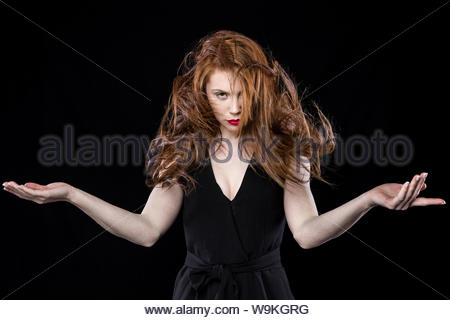 Young woman with red lipstick wearing a black jumpsuit on a black background flicking her long red hair, taken in a studio environment - Stock Photo