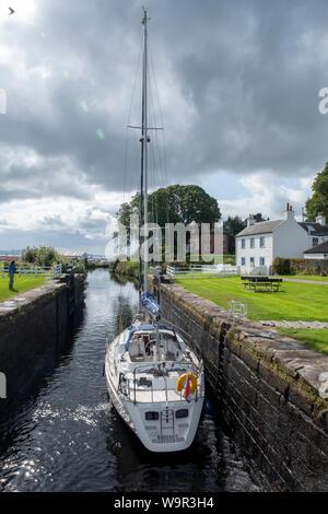 A yacht passes through a canal lock on the Crinan canal at Adrishaig, Argyll, Scotland. - Stock Photo