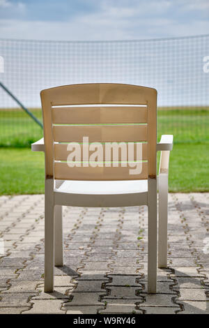 An empty white garden chair is faced out on some fields, meadows and a high fence on a sunny summer day - Stock Photo