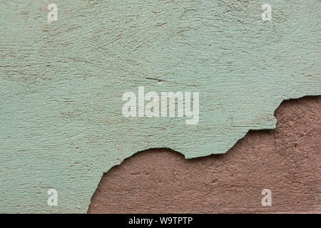 Green paint with crack revealing red wall below - Stock Photo