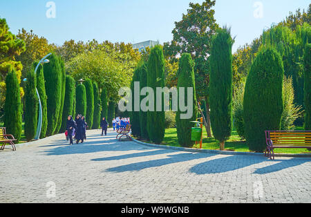 TEHRAN, IRAN - OCTOBER 25, 2017: The group of little Iranian schoolgirls, dressed in uniforms and hijabs, runs and plays during excursion to Laleh Par - Stock Photo