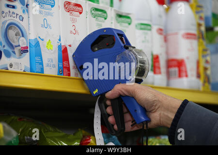 Buenos Aires, Argentina. 14th Aug, 2019. An employee marks milk packs with new prices after this week's economic turmoil. The stock markets in Buenos Aires have collapsed following the election defeat for President Macri's liberal government in the primary elections. The leading index S&P Merval lost 35.5 percent. The Argentine peso also broke in. As a result, prices rose in several sectors. Argentina is in a severe recession, with 10.1 percent unemployment and over 50 percent inflation. Credit: Claudio Santisteban/dpa/Alamy Live News - Stock Photo