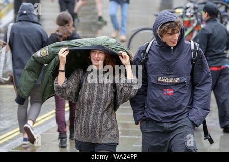 London, UK. 16th Sep, 2018. A woman covering herself under a green coloured jacket on a windy and rainy day in London. Credit: Steve Taylor/SOPA Images/ZUMA Wire/Alamy Live News - Stock Photo