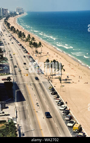 An aerial view of the sandy beach and Atlantic Ocean shows why one of the most popular American vacation destinations is Fort Lauderdale in subtropical southern Florida, USA. A parallel four-lane highway, State Route A1A, provides easy access to the year-round playground. However, since this photograph was taken in 1978, the beachside parking seen here has been eliminated in favor of an attractive pedestrian walkway that follows the long line of palm trees. Historical photograph. - Stock Photo