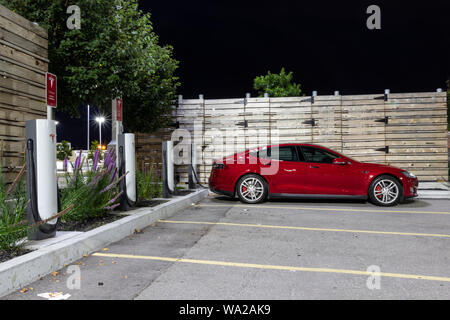 Red Tesla Model S charging at Tesla Supercharger under bright lights at night. - Stock Photo