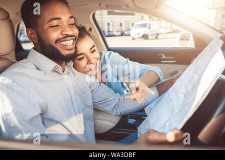 Travel by auto. Happy afro couple with map in car - Stock Photo