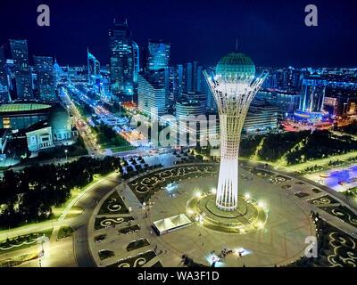 NUR-SULTAN, KAZAKHSTAN (QAZAQSTAN) - August 10, 2019: Beautiful panoramic aerial drone night illumination view to Astana city center with skyscrapers - Stock Photo