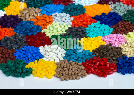 several dyed polymer granulates on white - Stock Photo