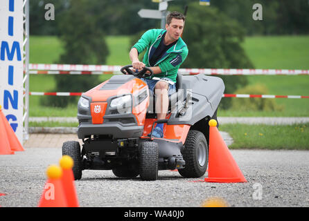 17 August 2019, Bavaria, Rückholz: A participant of the 1st Bavarian Championship in the riding mower obstacle race drives a slalom course during the race. In the Allgäu the 1st Bavarian Championship in the ride-on lawn mower obstacle course has begun. On Saturday (17.08.2019) more than 70 participants started in good weather until the afternoon. Photo: Karl-Josef Hildenbrand/dpa - Stock Photo