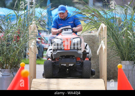 17 August 2019, Bavaria, Rückholz: A participant of the 1st Bavarian Championship in the riding lawn mower obstacle race crosses a bridge during the race. In the Allgäu the 1st Bavarian Championship in the ride-on lawn mower obstacle course has begun. On Saturday (17.08.2019) more than 70 participants started in good weather until the afternoon. Photo: Karl-Josef Hildenbrand/dpa - Stock Photo