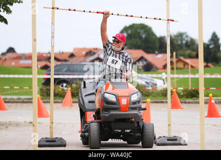 17 August 2019, Bavaria, Rückholz: A participant of the 1st Bavarian Championship in the riding mower obstacle race picks up a pole during his race. In the Allgäu the 1st Bavarian Championship in the ride-on lawn mower obstacle course has begun. On Saturday (17.08.2019) more than 70 participants started in good weather until the afternoon. Photo: Karl-Josef Hildenbrand/dpa - Stock Photo