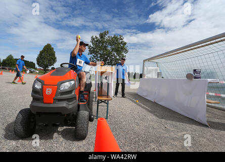 17 August 2019, Bavaria, Rückholz: A participant of the 1st Bavarian Championship in the riding mower obstacle race throws balls on cans during the race. In the Allgäu the 1st Bavarian Championship in the ride-on lawn mower obstacle course has begun. On Saturday (17.08.2019) more than 70 participants started in good weather until the afternoon. Photo: Karl-Josef Hildenbrand/dpa - Stock Photo