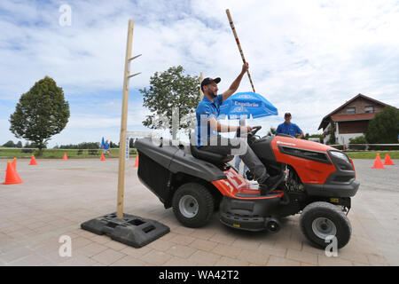 17 August 2019, Bavaria, Rückholz: A participant of the 1st Bavarian Championship in the riding mower obstacle race picks up a pole during the race. In the Allgäu the 1st Bavarian Championship in the ride-on lawn mower obstacle course has begun. On Saturday (17.08.2019) more than 70 participants started in good weather until the afternoon. Photo: Karl-Josef Hildenbrand/dpa - Stock Photo