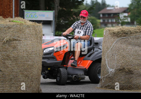 17 August 2019, Bavaria, Rückholz: A participant of the 1st Bavarian Championship in the riding mower obstacle race drives a course through hay bales during the race. In the Allgäu the 1st Bavarian Championship in the ride-on lawn mower obstacle course has begun. On Saturday (17.08.2019) more than 70 participants started in good weather until the afternoon. Photo: Karl-Josef Hildenbrand/dpa - Stock Photo