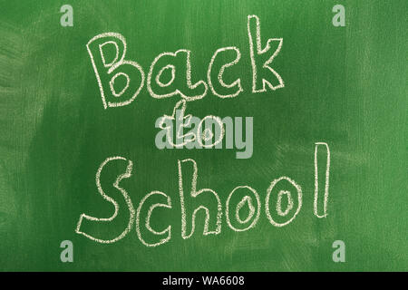 Back to school concept with written words in chalk on green blackboard. The beginning of the school year. Lettering - Stock Photo