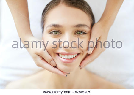 portrait of beautiful young woman smiling at camera while enjoying head massage in Spa - Stock Photo