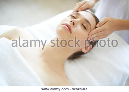 Portrait of beautiful young woman enjoying head massage in Spa - Stock Photo