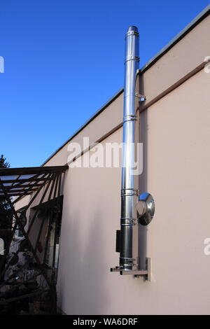 new stainless steel chimney on a house - Stock Photo