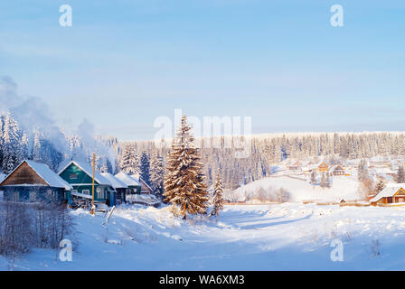 landscape - a Russian village in a winter valley on the bank of a frozen river on a frosty clear day - Stock Photo