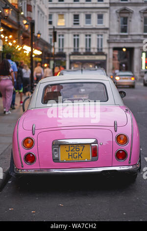 London, UK - August, 2019. A pink retro styled Nissan Figaro parked in a street close to Covent Garden in central London. - Stock Photo