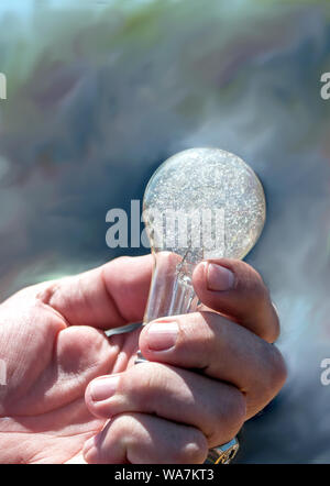 a man's hand holds an old, antique light bulb with crackled glass - Stock Photo