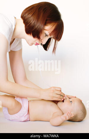 Mother using nasal aspirator for cute little baby lying on bed at home. Health care concept - Stock Photo