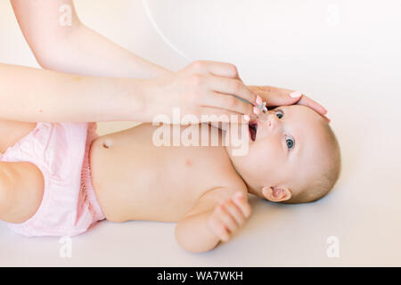 Mother using baby nasal aspirator. She is doing a mucus suction to four months baby girl - Stock Photo