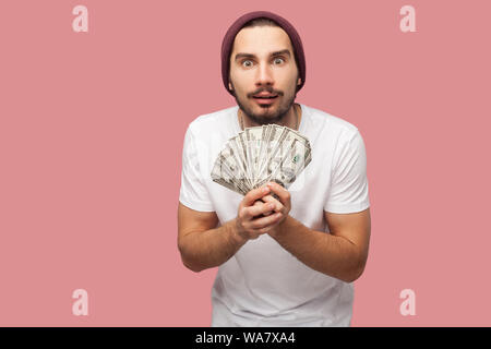Money. Portrait of suprised handsome bearded young hipster man in white shirt and casual hat, stand, holding fan of dollars with big eyes. Indoor, iso - Stock Photo