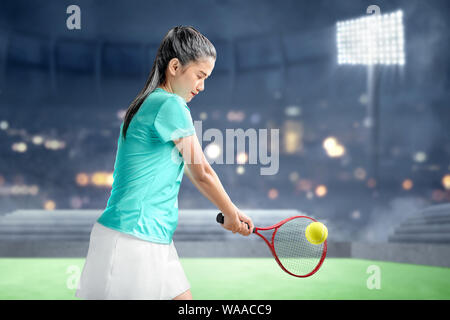 Asian woman with a tennis racket in her hands hit the ball on the indoor court - Stock Photo