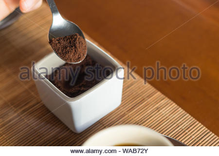 Close up of a spoon taking some ground coffee along a cup of coffee in a wooden desk - Stock Photo