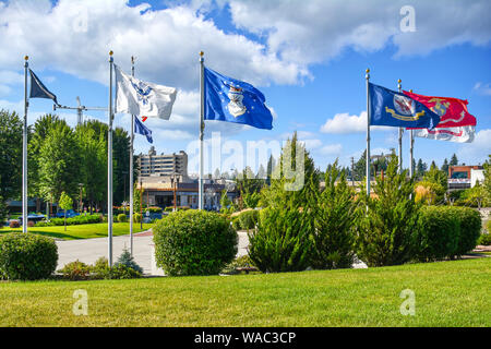 The flags of the branches or military fly near a resort in the mountain town of Coeur d'Alene, Idaho - Stock Photo