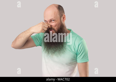 Bad smell. Portrait of confused middle aged bald man with long beard in light green t-shirt standing, blocking his nose and looking at camera. indoor - Stock Photo