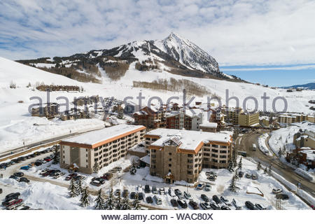 The Grand Lodge Hotel with the Crested Butte Mountain Resort ski area in the distance. - Stock Photo